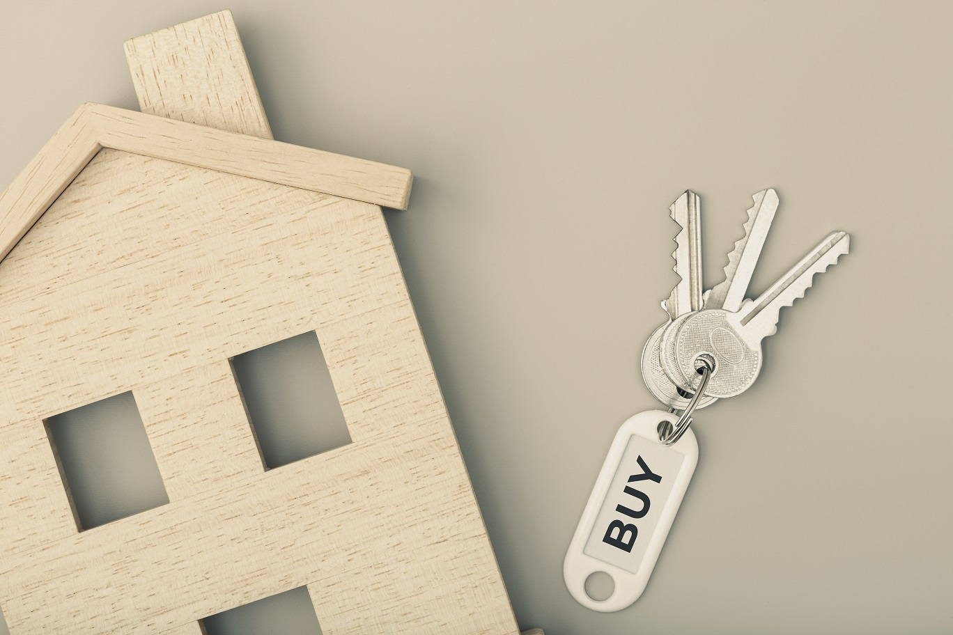 Buying a house concept. Real estate market. House icon with keys. Copy space. Top view