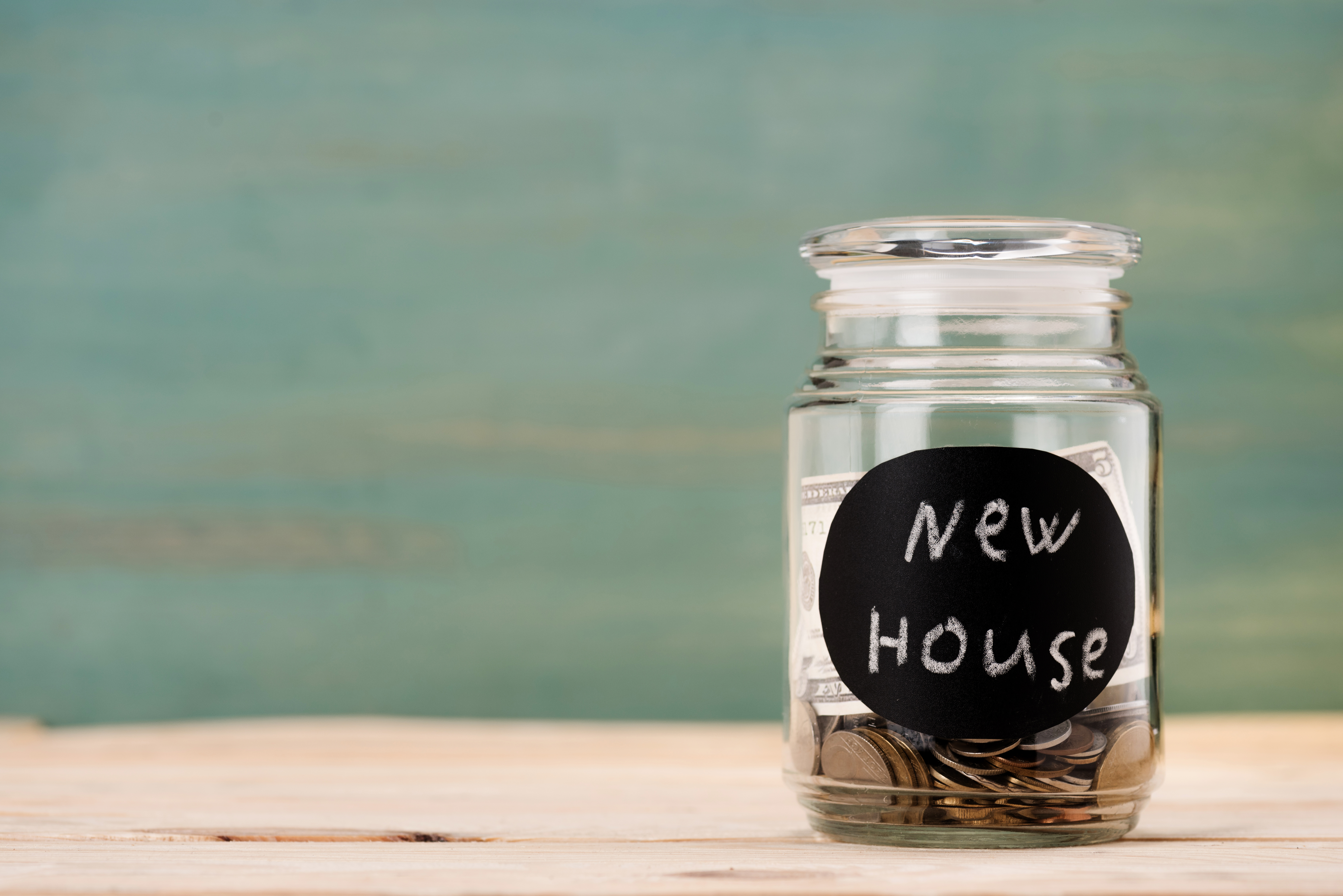 coins in glass can with sign new house on wooden table