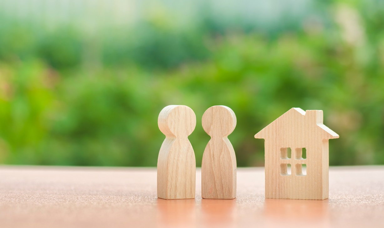 Two wooden figures of people and a house on a nature background