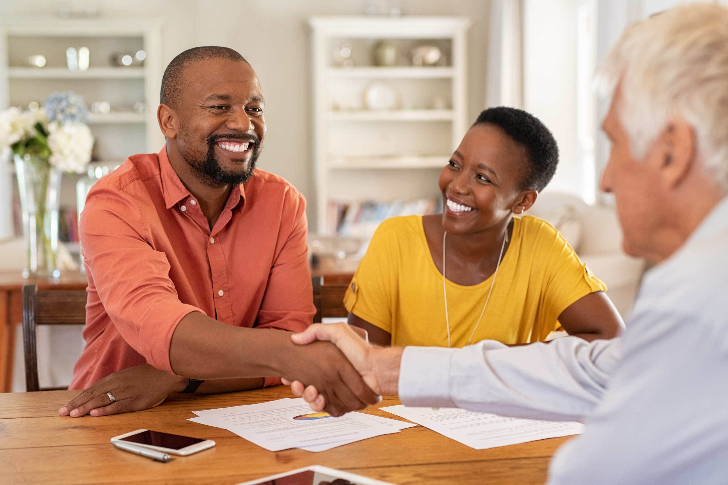 Mature man shaking hands with home loan advisor
