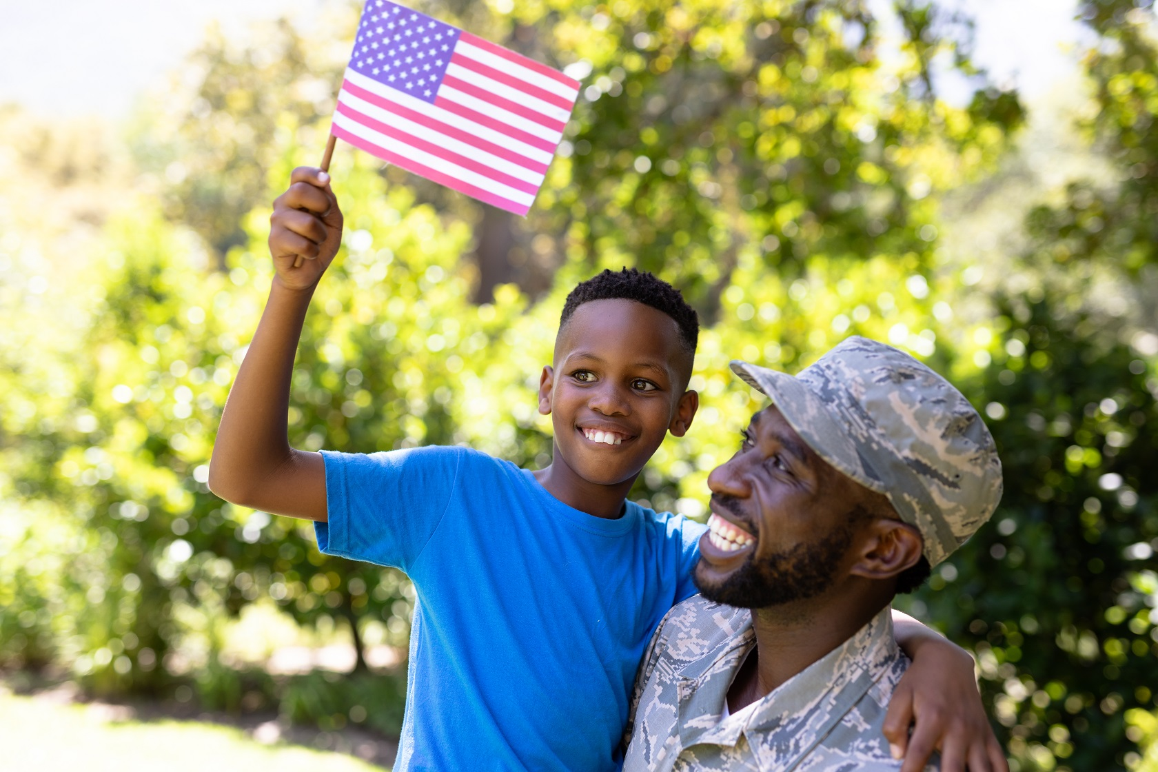 military father with his son holding an American flag